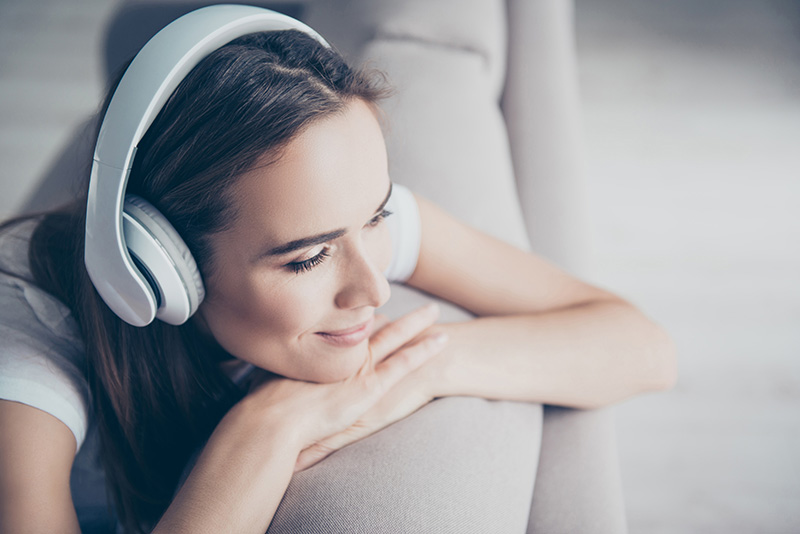 Chillout, satisfaction, therapy, wellness, leisure, lifestyle mode. Charmed adorable brown haired adorable model enjoying to the stereo sound in big modern ear phones in a room, nice break, good-day